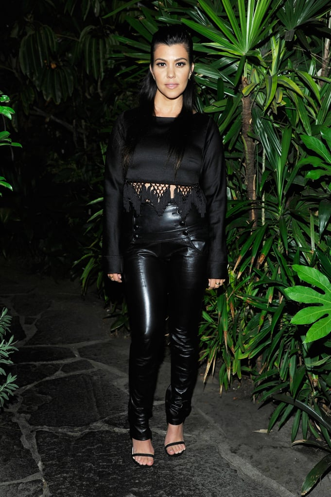 Kourtney Kardashian contrasted Khloé in all black. Her high-waist button-front leather pants met a satin long-sleeved crop top, complete with fringe detail. She finished her look with simple black sandals.