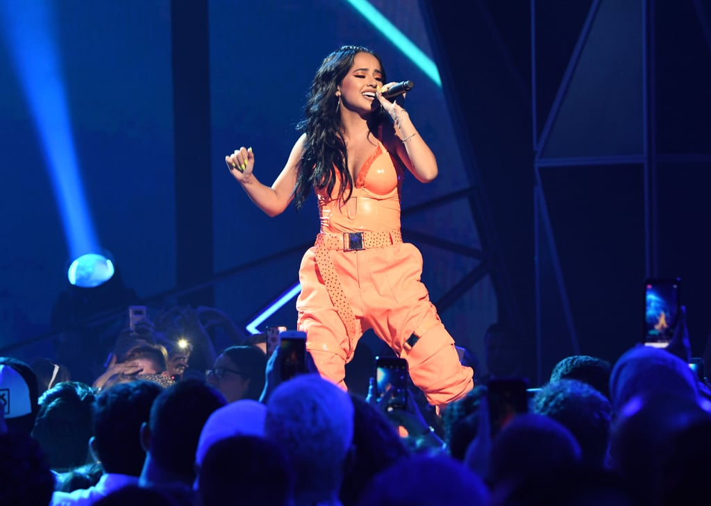 "Becky G is wearing the beauty trend celebrities can't seem to get enough of this Summer — neon hues across manicures and eyelids.  The ""Mad Love"" singer performed at Amazon's Prime Day concert in a monochromatic neon orange outfit with matching florescent eyeliner and shimmery burnt orange eye shadow.  The singer didn't stop there for her bright look. Becky G also wore long, square neon green nails, a hue also seen on celebrities like Rihanna, Billie Eilish, and Dua Lipa. She paired her bright look with a matte nude lipstick to finish off her bold look.  Check out the star's vibrant look ahead."