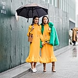 Camila Coelho and Aimee Song both wearing the same yellow Tibi dress outside the brand's show.