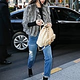 Rolling up her denim to reveal black patent boots and toting her Chanel backpack.