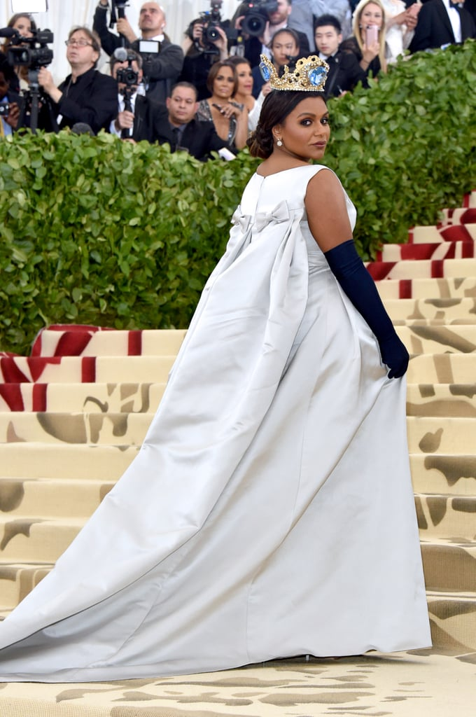 "Mindy Kaling waltzed into the 2018 Met Gala like the queen that she is. The 38-year-old actress arrived at the very exclusive, high-drama event in a silver Vassilis Zoulias gown and navy elbow-length gloves. Tying in the religious — and slightly medieval — ""Heavenly Bodies"" theme, Mindy wore an opulent crown with massive blue jewels.  Though Mindy has attended the Met Gala several times years prior, this is her first time since filming Ocean's 8, which is primarily centered on the event! With her other costars in attendance — ahem, Rihanna — it looks like the gang is back together for fashion's biggest night.       Related:                                                                                                           Every Look at the 2018 Met Gala Was Bold Enough to Leave an Impression"