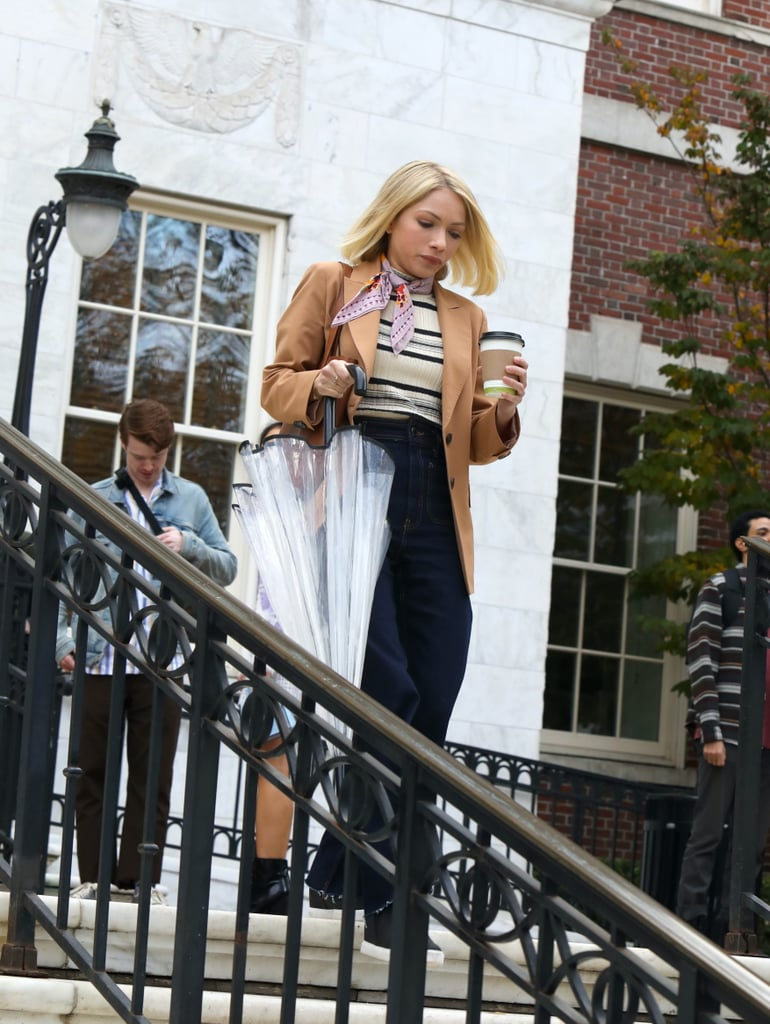 """That being said, you'll probably notice there are a few homages to the cast's original outfits from the opening scenes of the reboot. For example, Tavi Gevinson, who plays Kate, replicates an outfit made famous by Blake Lively's Serena in the Gossip Girl pilot. She wears S's iconic tan jacket, striped top, and scarf around her neck, just like Serena does in Grand Central Station when spotted by Dan Humphrey. """"We first see [Tavi's character] paying homage to Serena's first outfit. Here's this teacher coming in, and maybe she knows that she's emulating Serena, who was the It girl. Maybe she thinks it's cool to be dressing like Serena, but it's actually a little bit dated,"""" Eric said."""