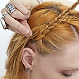 While holding first braid securely to your head, pull your second braid up and across the first one.