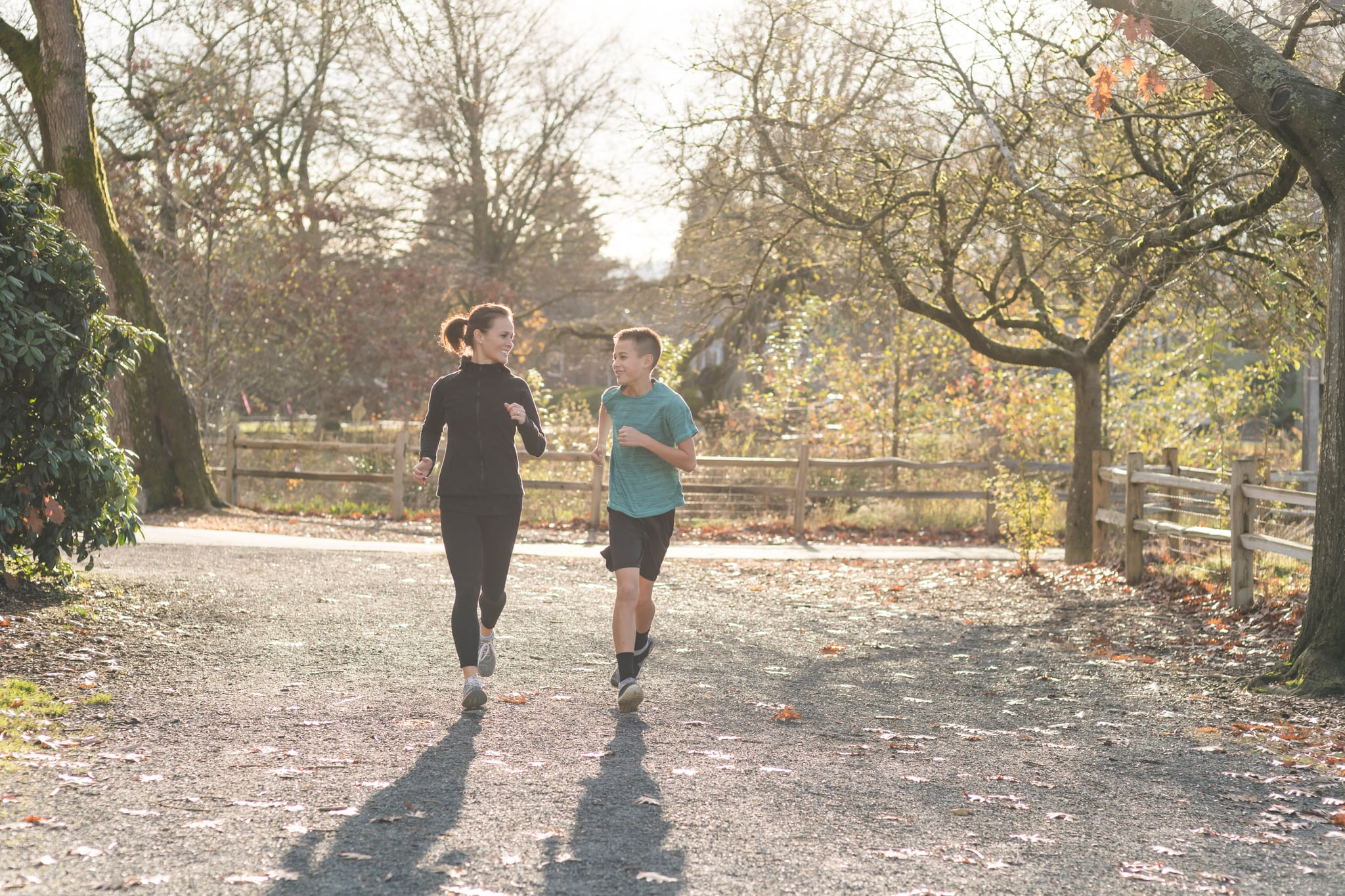 An elementary-age boy goes jogging with his mom in the city park on an autumn morning. They are looking at each other affectionately for a moment as they run. There are leaves scattered on the ground.