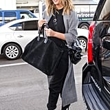 Chrissy wore a chic tweed duster coat with a black shirt, matching jeans, and a pair of sexy lace-up boots. She finished her look off with a black tote bag and Svelte Metals hoops.