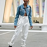 Futuristic sneakers and paper-bag-waist pants feel sporty-sleek with a cropped denim jacket.