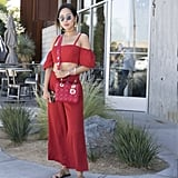 Aimee Song wearing a Dior bag and red coordinate set at the Revolve pool party.