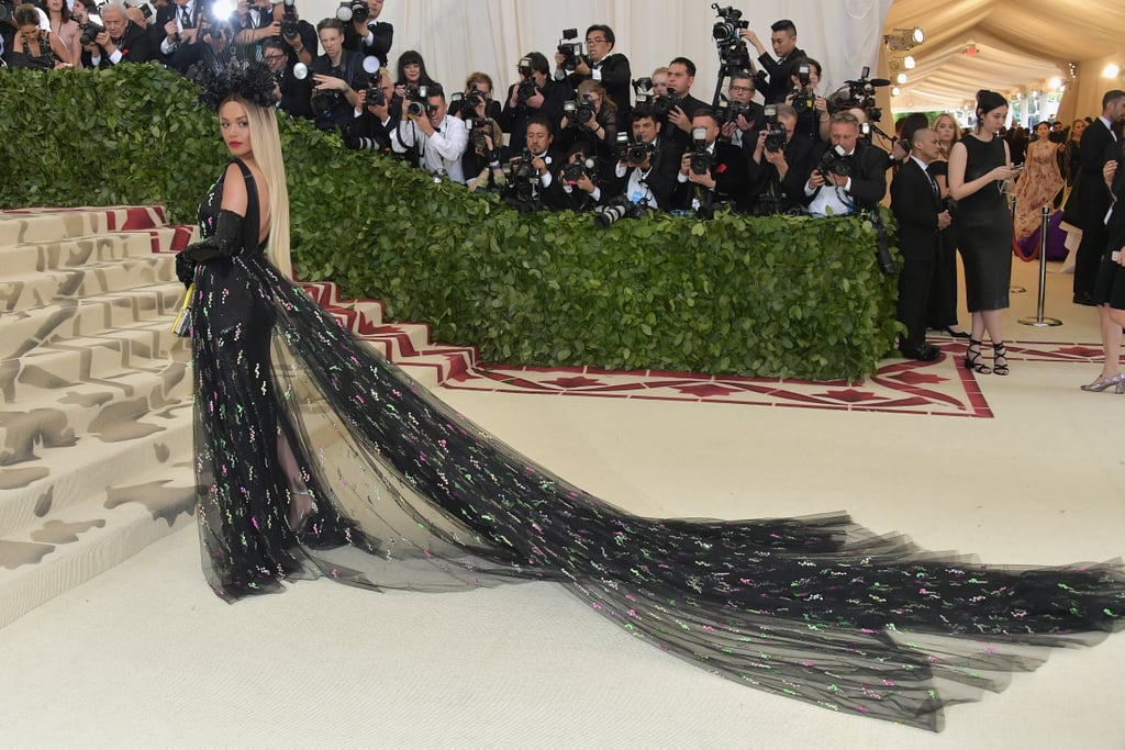 Stars always save their best looks for fashion's biggest night: the Met Gala. With Amal Clooney, Rihanna, and Donatella Versace co-hosting alongside Vogue EIC Anna Wintour this year, you better believe celebrities brought their A game. Case in point? Rita Ora.  The singer walked the Met's iconic steps in a sheer black dress by Prada that made us do a double take. Rita's gorgeous gown featured a sequined skirt with a tulle train that looked like it went on for miles. She finished off her look with a matching headpiece and sequinned gloves. Read on for a closer look.      Related:                                                                                                           The Most Unforgettable Met Gala Moments