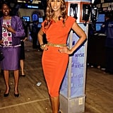 Iman, in a body-perfect tomato red Victoria Beckham Collection dress — the gold belt accent is key.