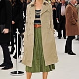 Poppy Delevigne wore a slick trench over a belted skirt on her way inside the Burberry show.