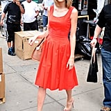 Taylor covered up in a feminine flared dress that matched her vibrant orange lip color.