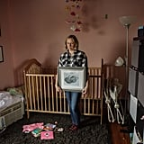 """Kristin holds a photo of her daughter, Abby, in her unfinished nursery. Her death was unexpected and traumatic. Instead of finishing Abby's nursery, the room became a chaotic storage area, mirroring the chaos her death brought into their family."""