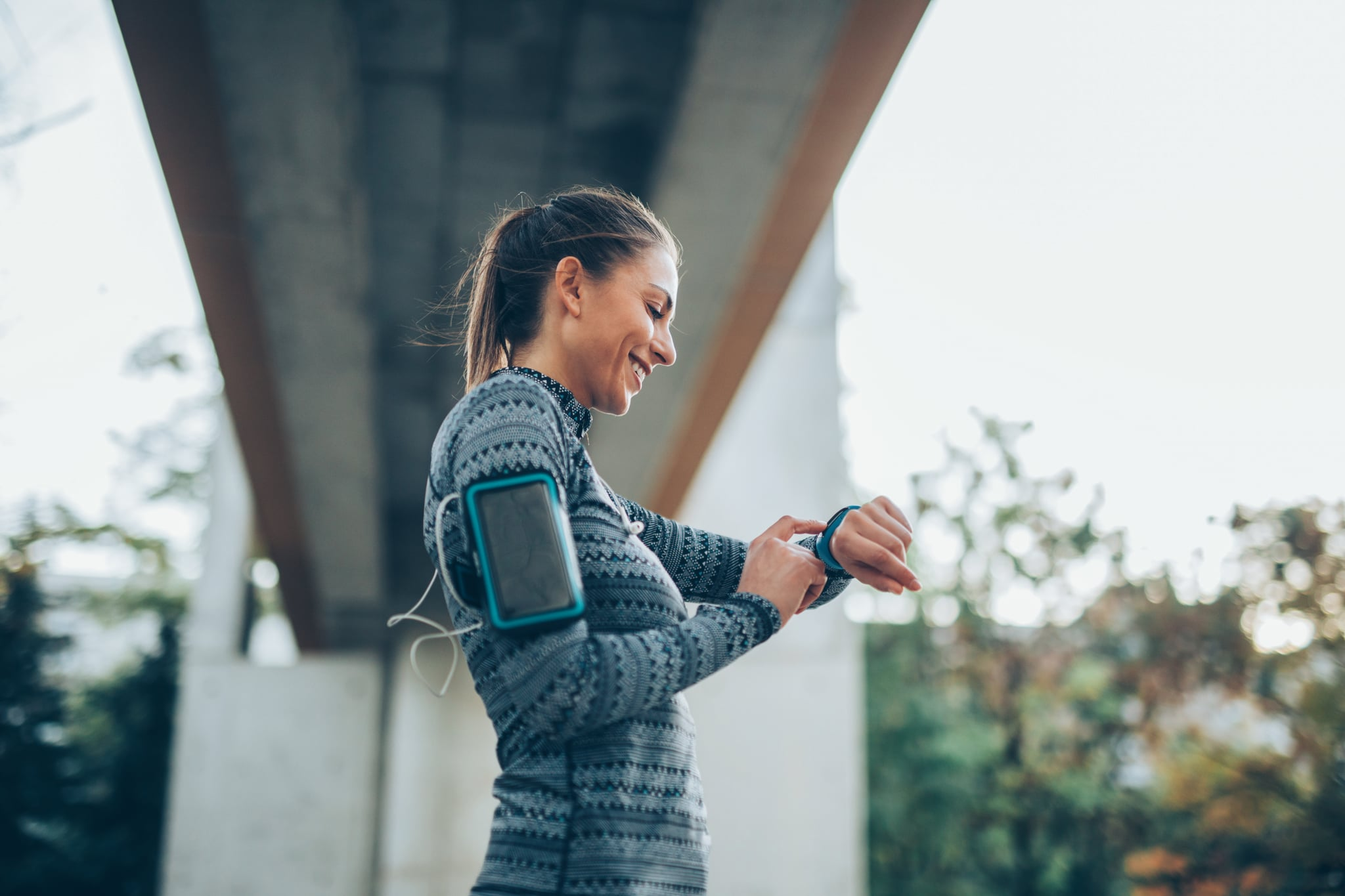 Sportswoman using a smart watch outdoors.