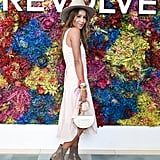 Julie Sarinana wearing a flouncy dress, wide brim hat, and Chloé bag at the Revolve festival.
