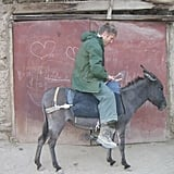 Here, he tries out some local transportation in the country: a donkey.