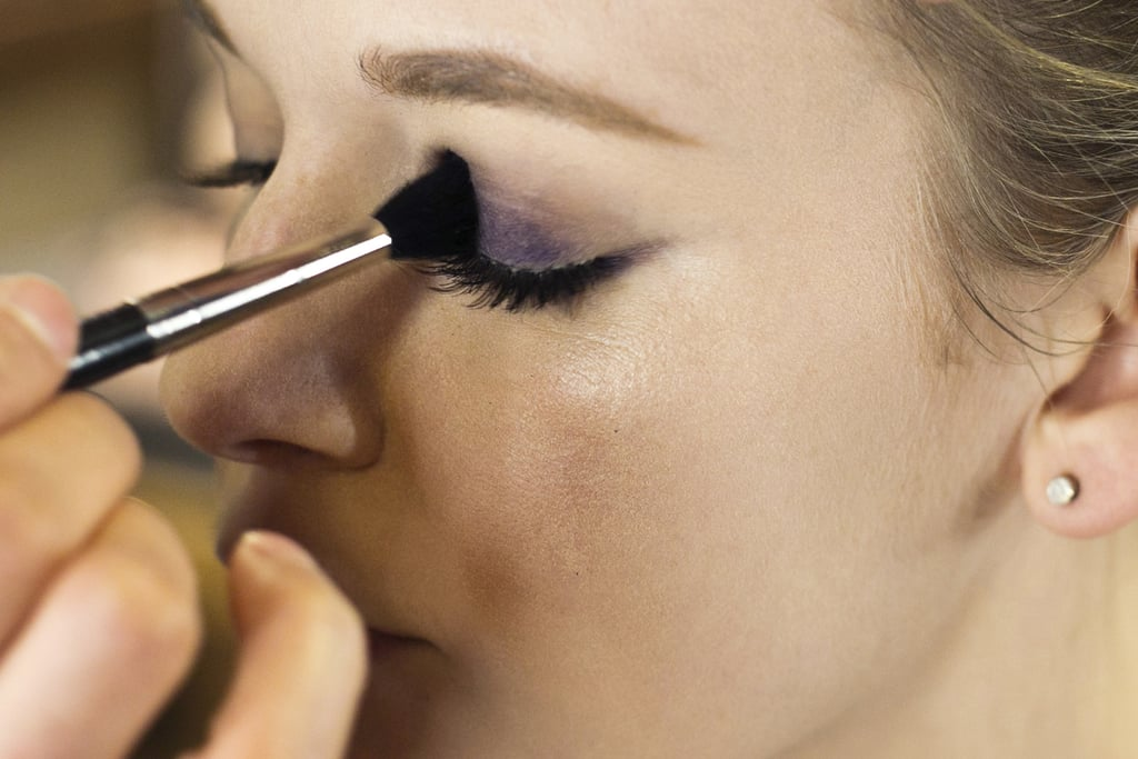 "Line the upper lash line with the same deep violet liner. ""I like to follow the contour of the eye shape instead making one straight line,"" Jennings says. Start with a thin line at the inner corner of the eye and create a gradually thicker line as it reaches the outer corner.  Next, ""stain"" the lid with the pencil to aid in forming a long-lasting color base for the eye makeup. Then go over the pencil with a brush to blend out the color before it sets."