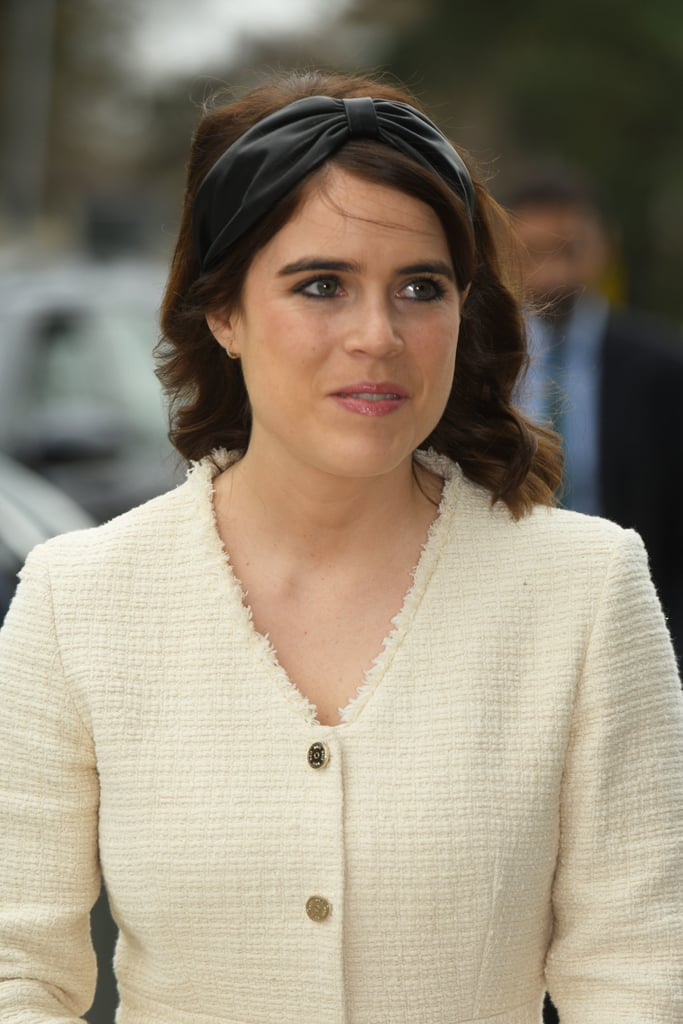Princess Eugenie's always been a fan of fashion-forward headwear, but over recent years, she's swapped the giant fascinators and big hats for slightly subtler designs. Both she and her sister, Beatrice, seem fond of wide fabric headbands as an alternative to hats, and recently, Eugenie's shown a particular love for a cool leather headband by Eugenia Kim. She first wore it for a trip to church on Christmas Day, and on Thursday, she reached for it again as she and her husband, Jack Brooksbank, joined her dad, Prince Andrew, for a visit to the Royal National Orthopaedic Hospital. Eugenie teamed her headband with the Maje White Tweed Style Trapeze Dress ($445) and black accessories including a Chloé handbag and heels. Though her original headband has now sold out, you can still get the look with some very similar styles. Keep reading for a closer look at Eugenie's statement headwear.