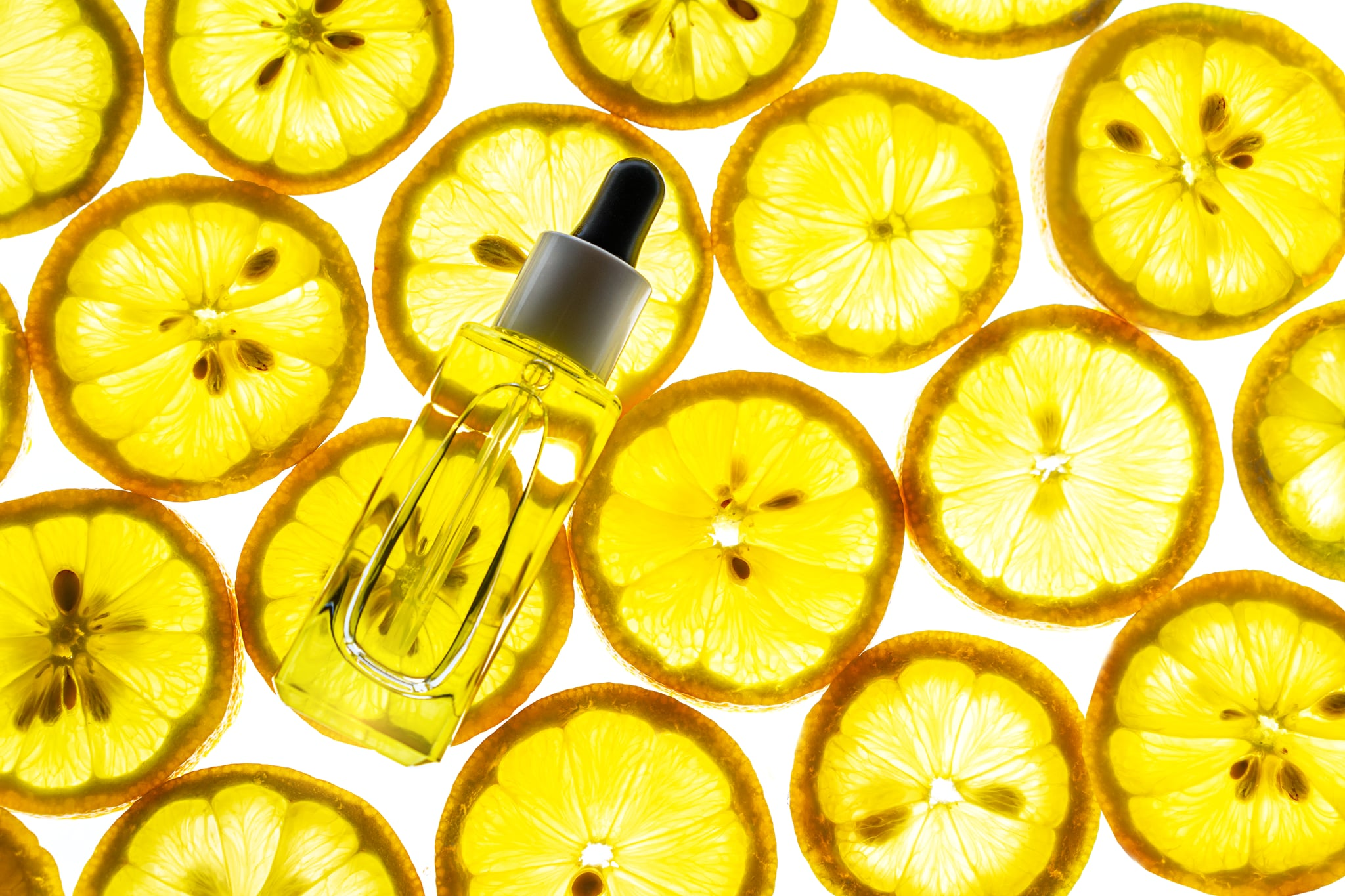 Natural vitamin c serum, skincare, essential oil product. Cosmetic with fresh juicy lemon fruit slice on lime background. Beauty product mock-up. Top view, flat lay.