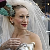 """""""I put a bird on my head!"""" Carrie goes for a sophisticated and sleek bridal beauty look with a slick up 'do and a pop of red on her lips."""