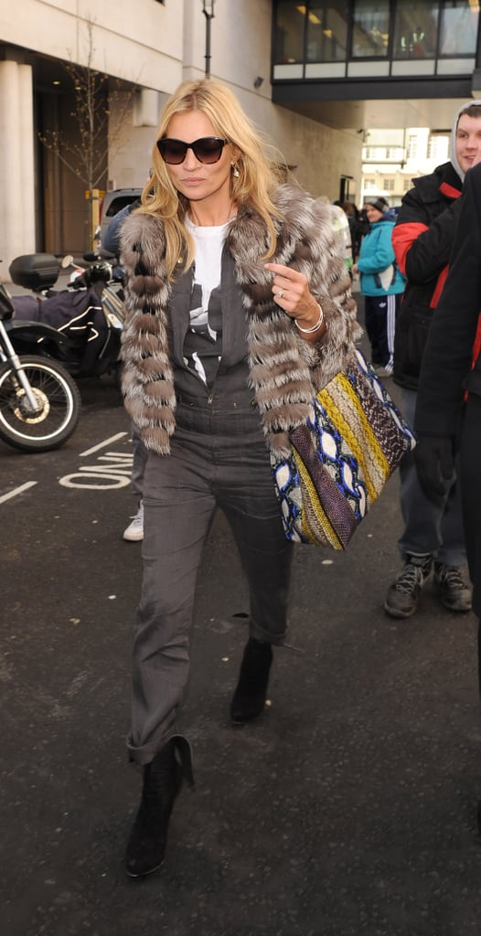 Kate Moss strutted through the streets of London in a grey jumpsuit, a fur coat, and a multi-coloured snakeskin bag.