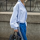 With a Shirt Twisted Off-the-Shoulder and a Designer Satchel
