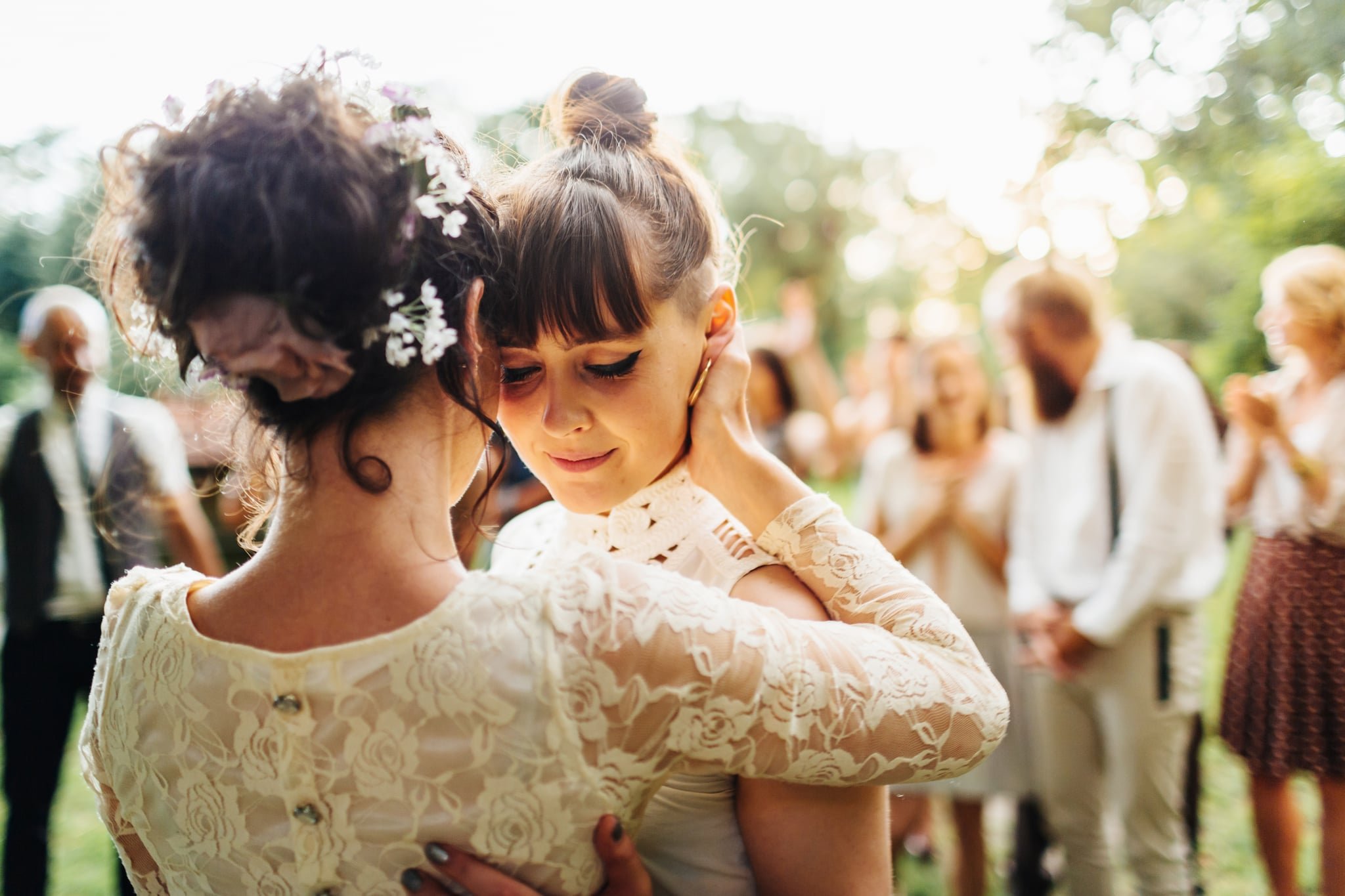Newlywed lesbian couple dancing together the first dance after their wedding ceremony. Family and friends are visible in the background