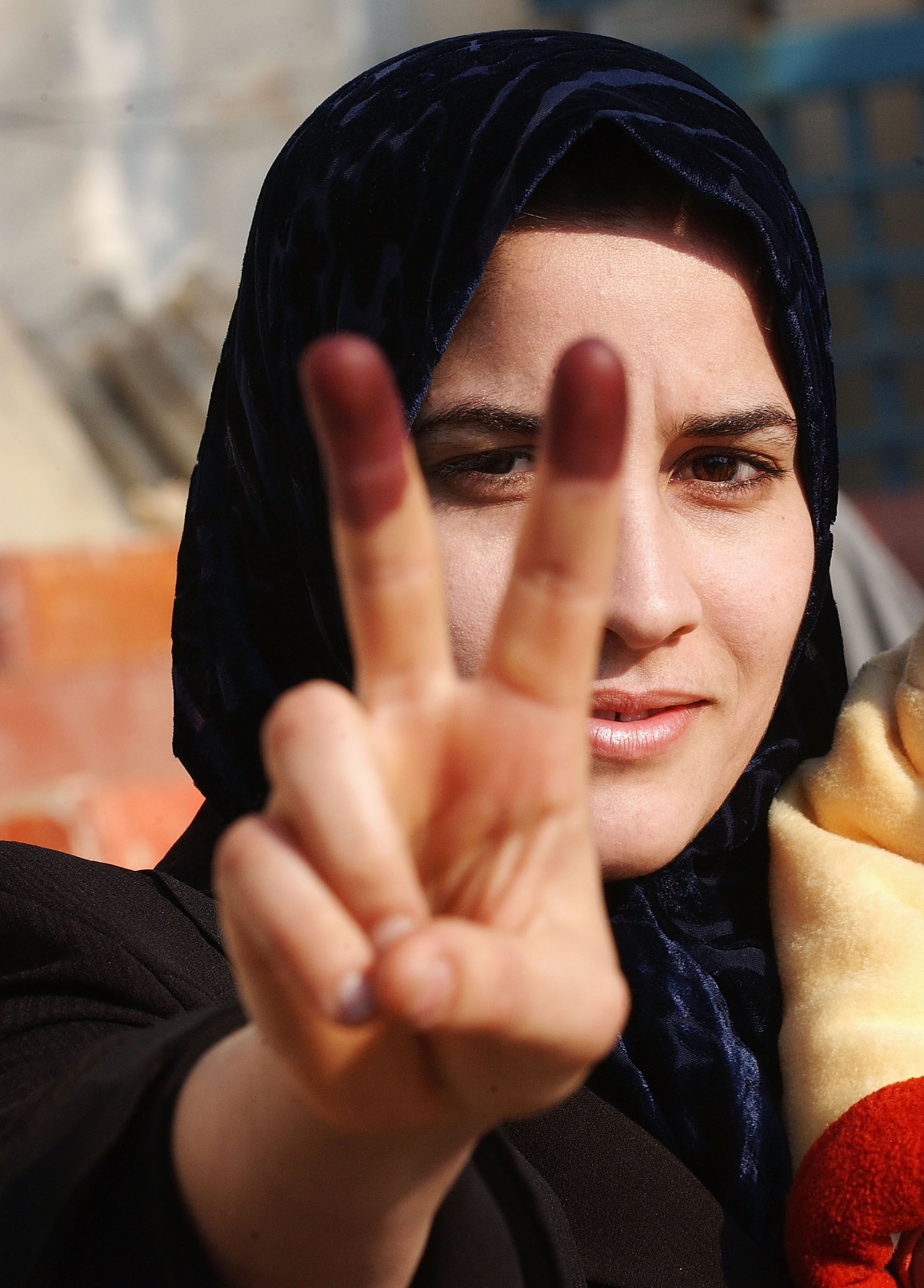 An Iraqi woman displays her inked fingers after voting on December 15, 2005.