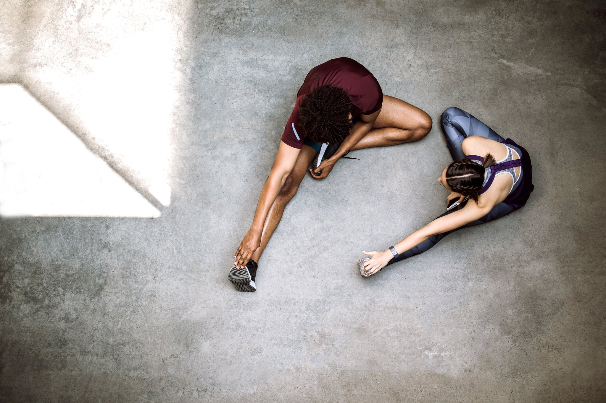 Attractive woman and handsome Afro man sitting on floor, stretching before morning jogging