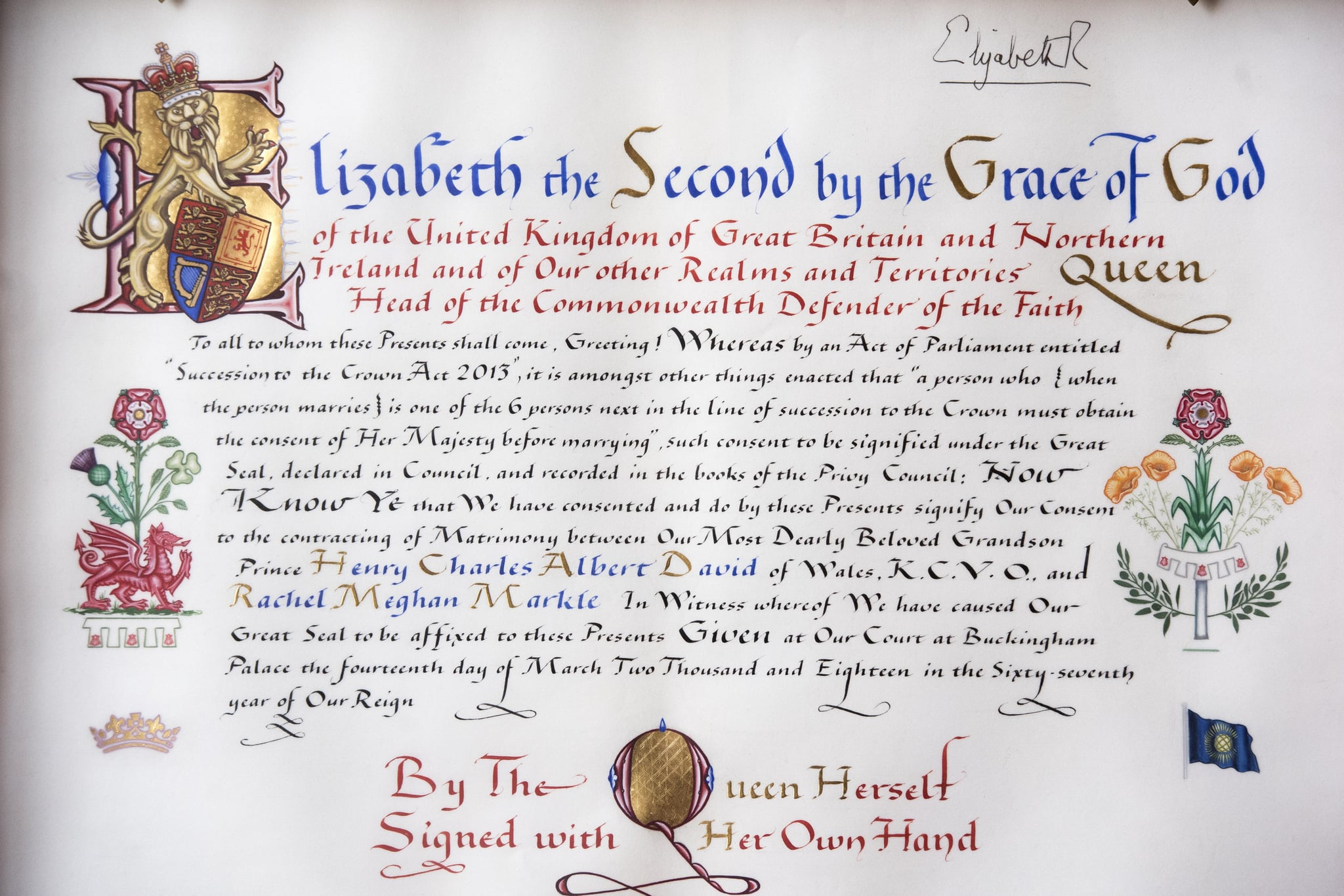 A picture taken at Buckingham Palace in London on April 12, 2018 shows the text and marginalia of the Instrument of Consent, an official State document that records the Queen's formal consent to Prince Harry's forthcoming marriage to Meghan Markle. - The Instrument of Consent is a hand-written document which records Britain's Queen Elizabeth II's consent to the marriage of Prince Harry and Meghan Markle. The document is hand-written and illuminated on vellum and sealed with the Great Seal of the Realm. The Queen's signature,