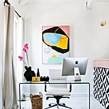 """""""For the office area, we maximized the space by using a clear desk and added a pop of color with an abstract art piece. We chose a blush cushion for the bed to cater to Shay's feminine side, while softening the edges of the tile,"""" Matt says."""