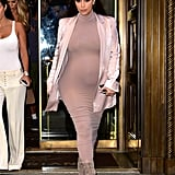 Kim's high-neck dress of choice is a bit more fitted and longer in length, but she paired her design with similar footwear and a mid-length neutral coat, too.
