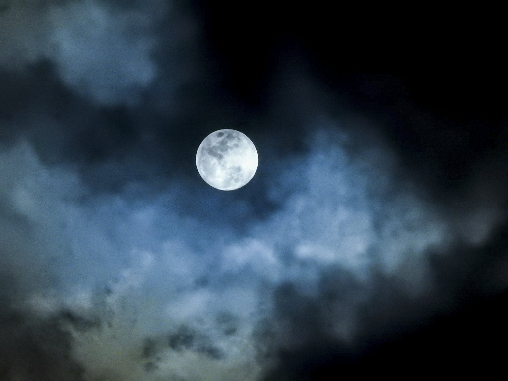 White blue in color, up close very detailed features of a full moon against a black backdrop of a sky. There are clouds lit up in front of the moon as they pass by.