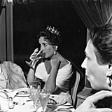 Elizabeth Taylor sipped a drink (while wearing a crown!) during a dinner at the 1957 festival.
