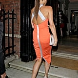 Victoria Beckham wore an orange Victoria Beckham dress.