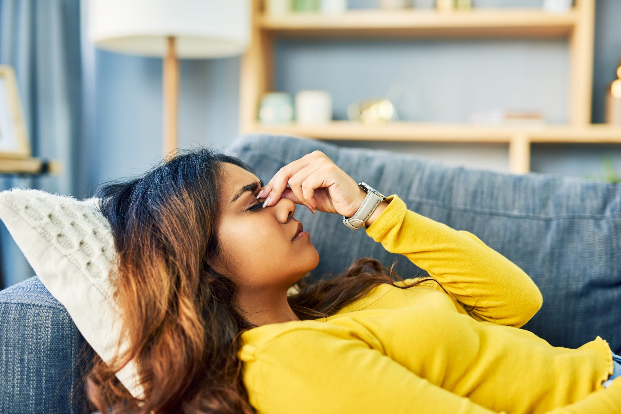 Shot of a young woman experiencing a bad headache while relaxing at home