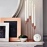 Hygge-fy your mantel with candles, mementos, and greenery