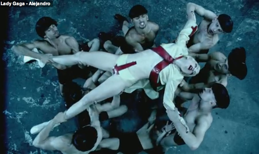 A melodramatic Gaga crowd surfs over her dancers. Note the red arrow pointing to her lady parts.