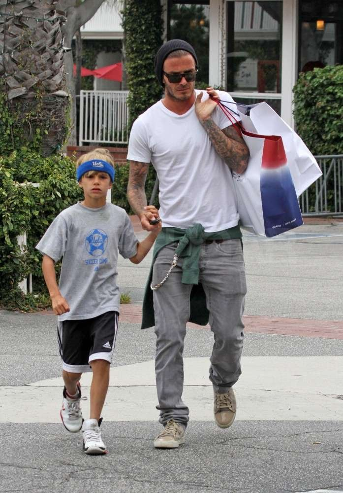 David Beckham and Romeo hit Fred Segal in LA today for a little father-son bonding time. The pair left hand in hand with a couple of shopping bags. Romeo looked sporty in a UCLA sweatband and a matching soccer camp t-shirt as they made their way to the car together. David is gearing up to hit the field himself this weekend, with the LA Galaxy taking on the San Jose Earthquakes tomorrow in a highly anticipated matchup. David and Romeo fit in their guys-only excursion this afternoon as the Beckham boys get closer to welcoming a new addition to the family. Victoria Beckham is expecting a baby girl in just a few weeks! In the meantime, David has been spending lots of time with his three sons close to their California home, cheering them on as they practice their soccer skills and taking them out to play with the family's dogs. Victoria also joined in on the family fun when they all checked out the premiere of Cars 2 over Father's Day weekend.