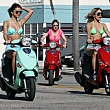 Vanessa Hudgens and Selena Gomez wearing bikinis and riding scooters.