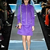 Walking in Moschino wearing a purple outfit and colorful pillbox hat.