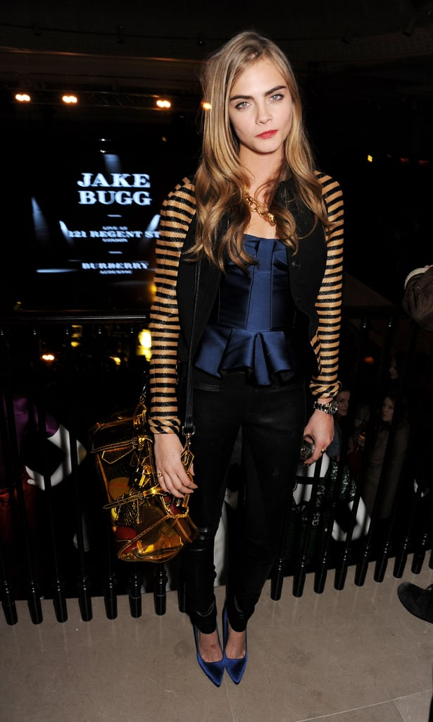 Cara Delevingne elevated the dress code at the Burberry Acoustic Presents event in London by donning a stripe-sleeved varsity jacket and a navy satin Burberry bustier with black leather pants and sapphire satin pumps. The blonde stunner accessorized her party style with a fox link necklace and a stunning gold mirrored satchel, both by Burberry.
