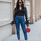 A tried-and-true combo: polka-dot top, high-waisted jeans, heels, and a bright bag.