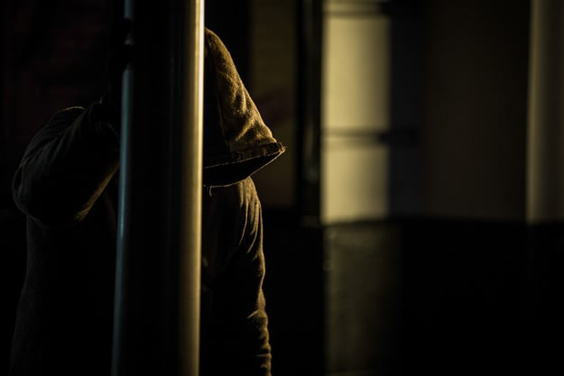 A figure looms in the shadows.