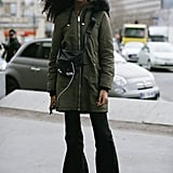 Look effortless off duty in an army-green anorak, flared jeans, and sneakers.