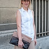 A fedora and an oversize Prada clutch lent a downtown-cool to a classic white button-up and pleats.