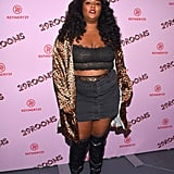 Lizzo transforms a simple black skirt by pairing it with a lace tube top, a leopard-print jacket, and a pair of supercute knee-high boots.