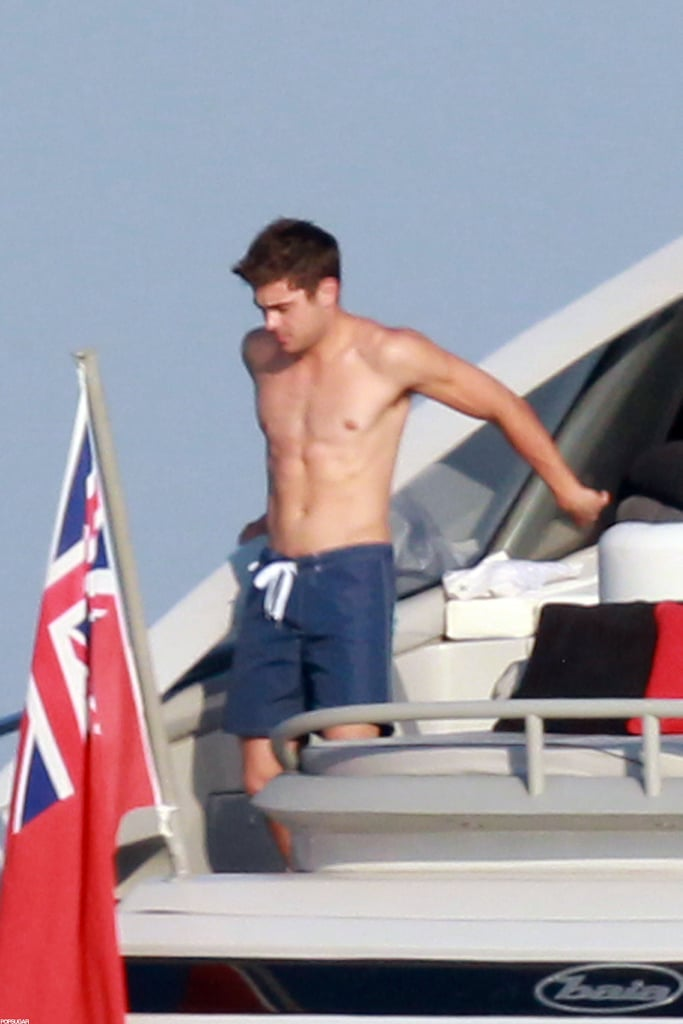 Zac Efron marked the Fourth of July with friends in the French Riviera today. The actor, sporting bright blue Ray-Bans and a mustache, was spotted having lunch with a group of guys at St.-Tropez's Club 55. The restaurant is a favorite among celebs, and after the meal, a barefoot Zac made his way down the dock and hopped in a waiting boat. Once on his yacht, Zac stripped down to show off his sexy six-pack. He lounged shirtless on the deck and chatted with friends.  This is the second trip to the South of France that Zac's made in recent months. He also attended the Cannes Film Festival in May in support of his upcoming movie The Paperboy. Zac's current trip overseas meant he missed out on his friend and former High School Musical costar Ashley Tisdale's 27th birthday party earlier this week in Malibu. Zac was on hand for the festivities last year, but this time around, Ashley celebrated with a bikini-clad Selena Gomez and her boyfriend, Scott Speer.