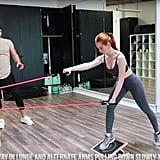 With one foot still situated on the slant board and holding onto the resistance bands, lean forward and pull your arms down one at a time.