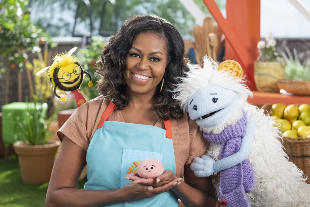 """Michelle Obama officially has her own Netflix show featuring two very adorable muppet friends, Waffles and Mochi. In the show — which is aimed at kids, though the former first lady says adults will love it, too — Michelle, or """"Mrs. O,"""" as she's called in the series, sends Waffles and Mochi on international adventures that are centered around cooking, global ingredients, and cultural experiences that revolve around food. """"This is something I've been working on for a while now, and I'm so excited to finally be able to tell you all about it,"""" Michelle wrote on Instagram. """"Allow me to introduce two new friends of mine: Their names are Waffles and Mochi. And on March 16, we'll be launching a new children's show on @Netflix called Waffles + Mochi. It's all about good food: discovering it, cooking it, and of course, eating it. These two will take us on adventures all around the world to explore new ingredients and try out new recipes. Kids will love it, but I know that adults will also get plenty of laughs—and some tips for the kitchen.""""      Related:                                                                                                           New Kids' Shows Coming to Netflix in 2021, Including Michelle Obama's Waffles + Mochi               According to Netflix, Waffles and Mochi are best friends who used to live in The Land of Frozen Food while pursuing their shared dream to become chefs. However, everything they cooked was made of ice, that is, until grocery owner Mrs. O hires them """"as the freshest employees of a whimsical supermarket."""" """"Whether they're picking potatoes in the Andes of Peru, sampling spices in Italy, or making Miso in Japan, these curious explorers uncover the wonder of food and discover every meal is a chance to make new friends,"""" reads the Netflix description. """"I'm hopeful that this delightful show can bring a bit of light and laughter to homes around the world."""" — Michelle Obama """"In many ways, this show is an extension of my work to suppo"""