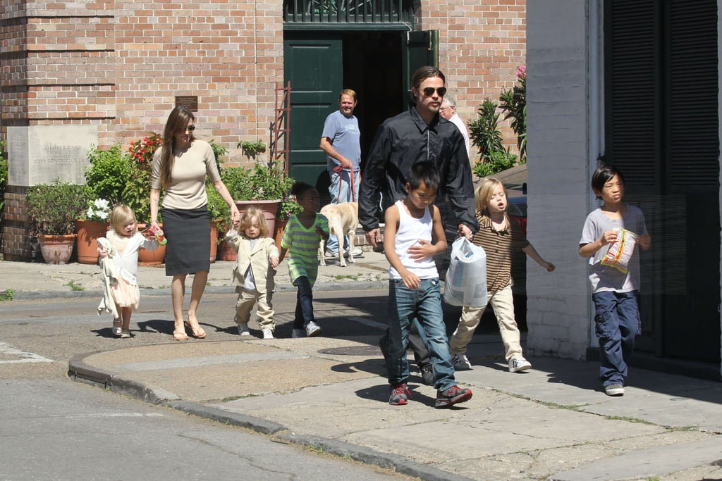 Angelina Jolie and Brad Pitt brought all six kids along for a trip to the market in New Orleans on Sunday. Angelina arrived with Pax, Maddox, Zahara, Shiloh, Knox, and Vivienne on Friday to join Brad where he has been shooting Cogan's Trade. Pax led the way with his snack while Angelina held hands with the twins in the rear. Knox and Vivienne are so cute in their dressy outfits —check out video of their adorable day. Zahara and Shiloh are both rocking stripes and Maddox is such a little man in his tank. Brad's hair and goatee are for his role, but he skipped the slicked-back look for the outing with his family.